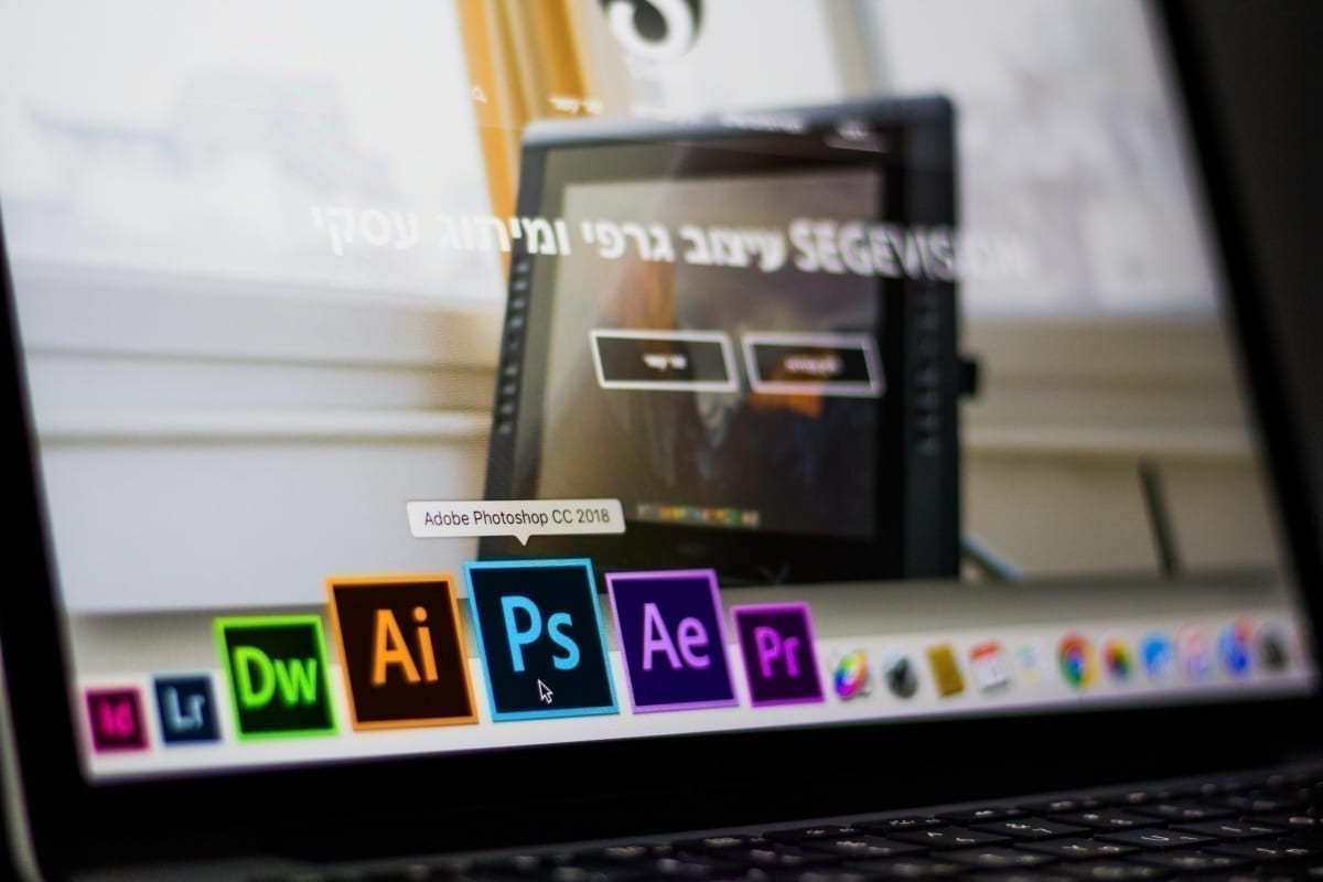 turned on laptop on desktop with hovered adobe photoshop cc 693892 scaled